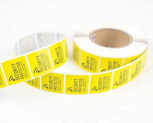 A roll of bright yellow RFID warning labels.