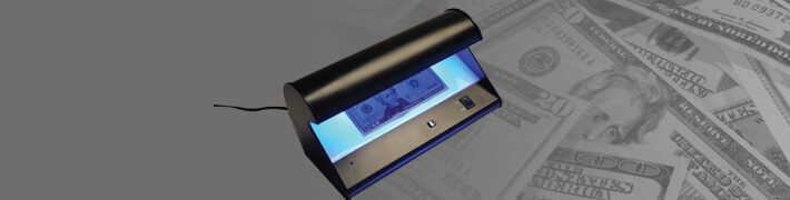 Counterfeit money detector scanning a $20 bill with $20 bills in the background.