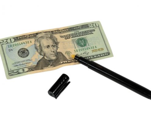 A counterfeit detector pen being used on a $20 bill.