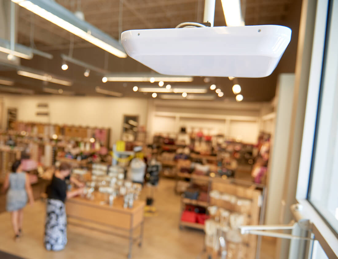 Close up of a ceiling-mounted RFID system—used for loss prevention—with a retail store in the background.