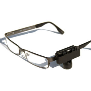 A black eyewear security tag is attached to a pair of wire frame glasses.