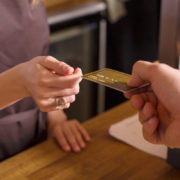 Man hands woman standing at cash register a golden credit card.