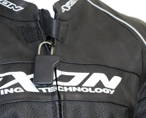 A black security tag with a steel shackle is shown attached to the zipper of a men's leather jacket.